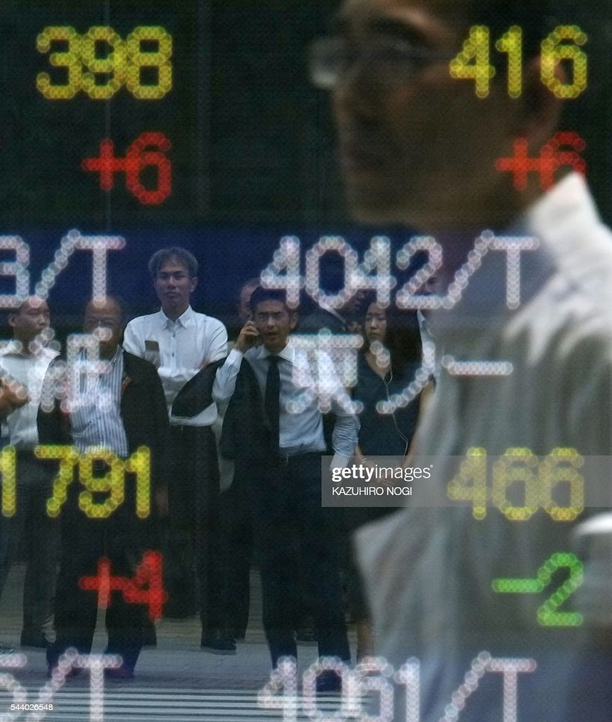 Pedestrians are reflected in the window of a securities company showing stock prices on the Tokyo Stock Exchange in Tokyo on July 1, 2016. Japan was clobbered with a one-two punch July 1 morning as weak data and a lacklustre business confidence report underscored the slowdown dragging on the world's number three economy. / AFP / KAZUHIRO