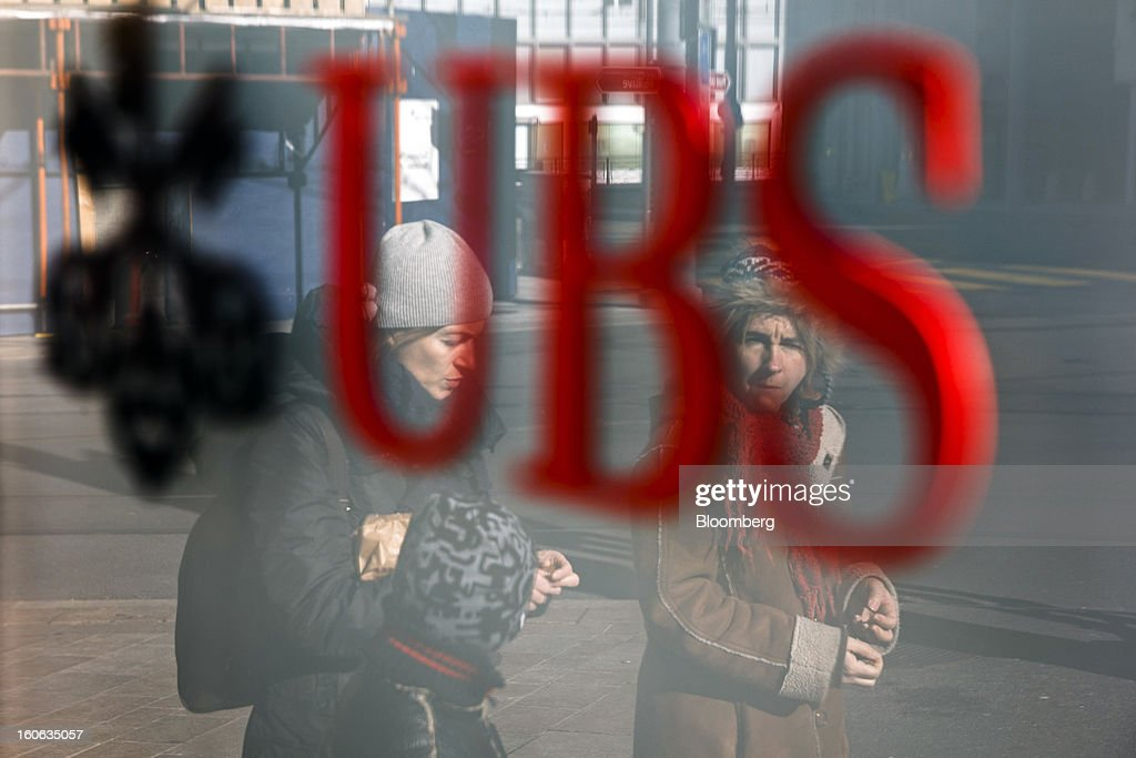 Pedestrians are reflected in the window of a UBS AG bank branch in Geneva, Switzerland, on Sunday, Feb. 3, 2013. UBS AG will report fourth-quarter results for the 2012 financial year on Feb. 5. Photographer: Valentin Flauraud/Bloomberg via Getty Images