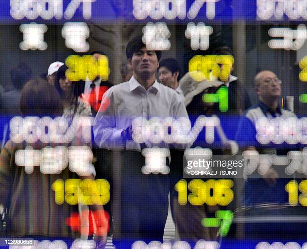 Pedestrians are reflected on a share prices board in Tokyo on September 6 2011 Asian shares tumbled on September 6 with Tokyo hitting a twoyear low...