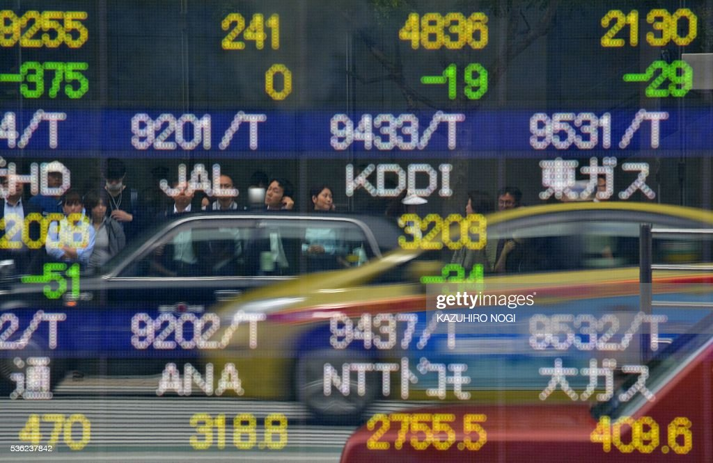 Pedestrians are reflected on an electronic stock quotation board at the window of a securities company in Tokyo on June 1, 2016. Tokyo stocks opened lower June 1 as profit-taking set in after five straight positive sessions, following a weak lead from Wall Street. / AFP / KAZUHIRO