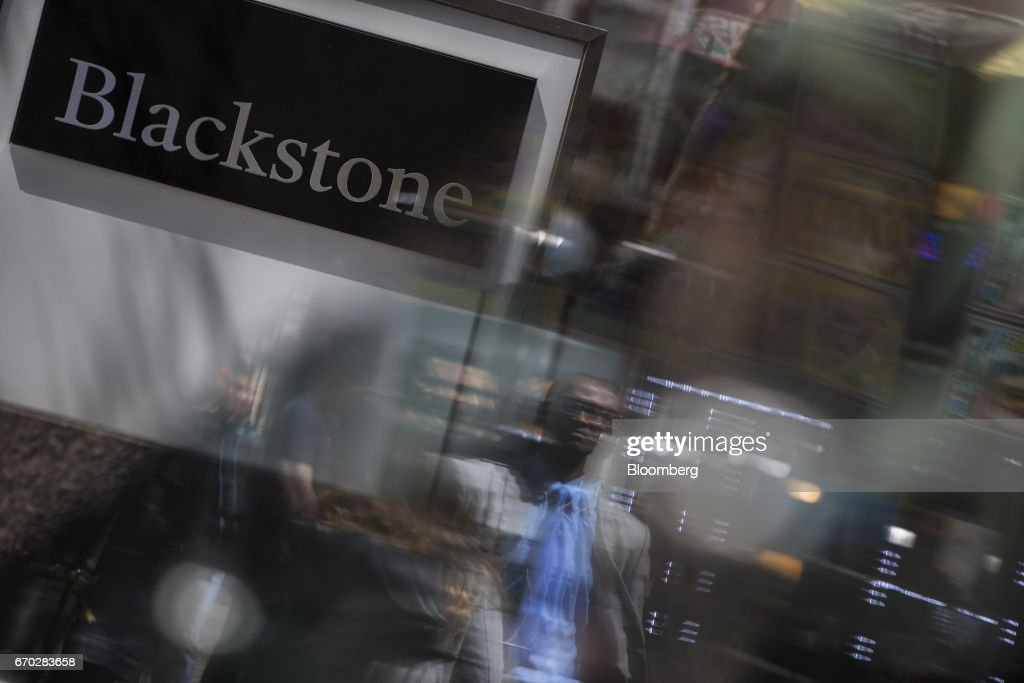 Pedestrians are reflected on glass in front of Blackstone Group LP headquarters in New York, U.S., on Friday, April 14, 2017. Blackstone Group LP is scheduled to release earnings figures on April 20. Photograph: Victor J. Blue/Bloomberg via Getty Images