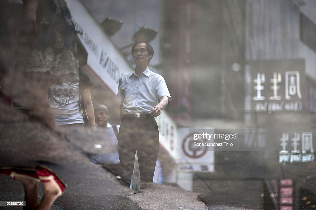 Pedestrians are reflected through a puddle on August 20, 2014 in Hong Kong, Hong Kong. A government-commissioned study headed by University of Hong Kong academic Nelson Chow Wing-sun proposed to fund HK $3,000 a month pension for every Hongkonger over 65, rich or poor, without a means test. The pension should be funded partly by contributions ranging from 1 to 2.5 per cent of employees' salaries, paid by employers and workers. One in three old people in Hong Kong lives below estimated poverty line some of them struggling to make a living collecting cardboard boxes and plastic bottles on the street.