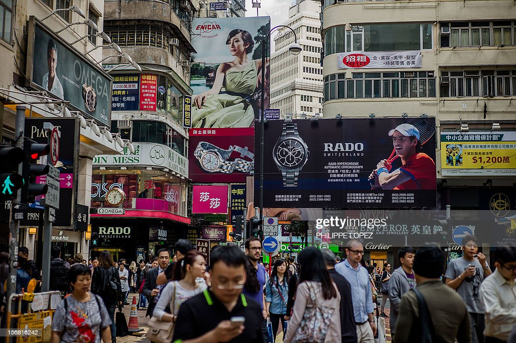 Pedestrians are seen at a busy intersection of Causway Bay disrtrict in Hong Kong on November 22, 2012. Hong Kong's bustling shopping district of Causeway Bay has knocked New York's Fifth Avenue off the top of the list of most expensive places to rent retail space in the world, new research showed in November 2012. AFP PHOTO / Philippe Lopez