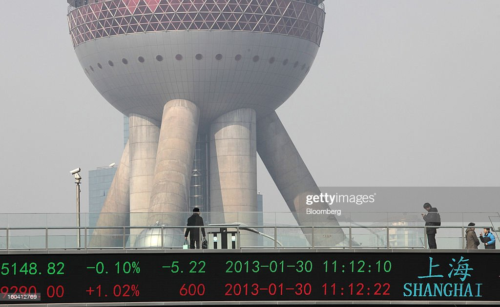 Pedestrians are seen on a bridge with a ticker displaying financial data in front of the Oriental Pearl Tower in the Pudong area of Shanghai, China, on Wednesday, Jan. 30, 2013. China's economic growth accelerated for the first time in two years as government efforts to revive demand drove a rebound in industrial output, retail sales and the housing market. Photographer: Tomohiro Ohsumi/Bloomberg via Getty Images