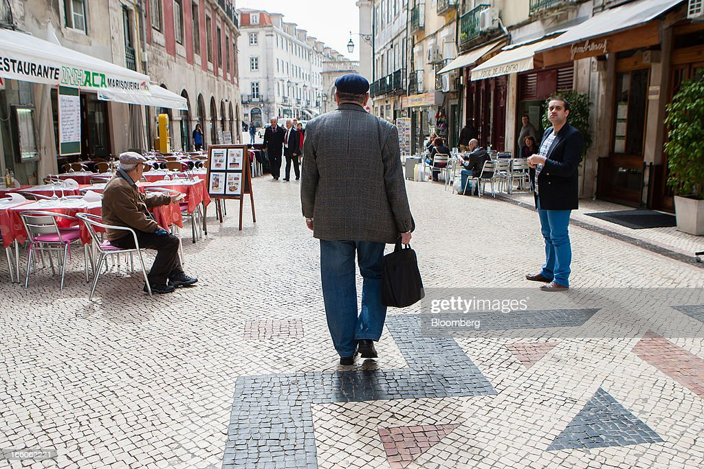 Pedestrians are seen on a main shopping street in Lisbon, Portugal, on Monday, April 8, 2013. Portugal will carry out more spending cuts this year after the Constitutional Court blocked a plan to suspend a monthly salary payment to state workers and pensioners. Photographer: Mario Proenca/Bloomberg via Getty Images