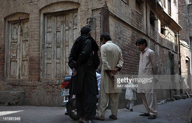 Pedestrians are seen on a street next to a dilapidated building in the old town section of Multan on March 17 2012 Multan one of the oldest cities in...