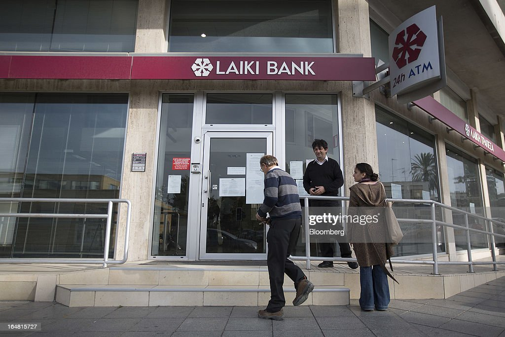 Pedestrians are seen outside a branch of Cyprus Popular Bank Pcl, also known as Laiki Bank, as banks open for the first time in two weeks in Nicosia, Cyprus, on Thursday, March 28, 2013. The Central Bank of Cyprus's capital controls will include a 300-euro ($383) daily limit on withdrawals and restrictions on transfers to accounts outside the country. Photographer: Simon Dawson/Bloomberg via Getty Images