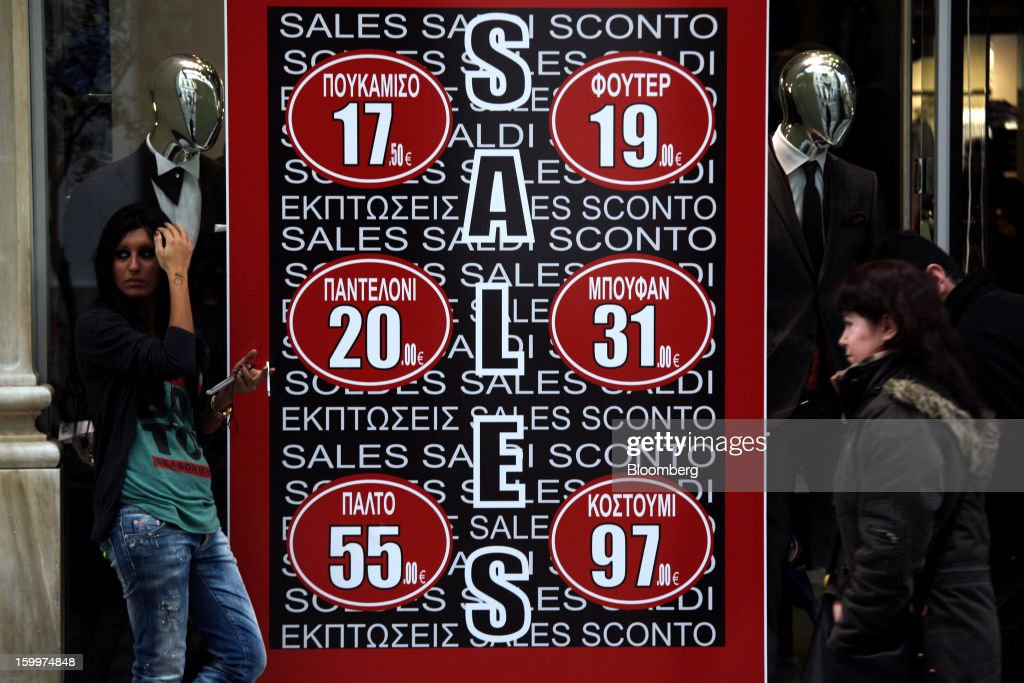 Pedestrians are seen outside a window display advertising discounts at a fashion store in Athens, Greece, on Thursday, Jan. 24, 2013. Greece's government has implemented budget cuts and economic reforms to tame a fiscal deficit that has led to bailouts from the European Union and the International Monetary Fund. Photographer: Kostas Tsironis/Bloomberg via Getty Images