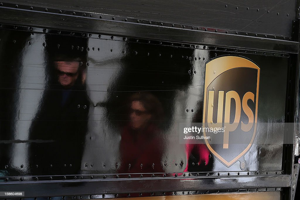 Pedestrians are seen reflected in the side of a UPS truck on December 20, 2012 in San Francisco, California. With less than one week to go before Christmas, today is expected to be the busiest day in the history of UPS and they are expecting to ship an estimated 28 million packages around the globe.