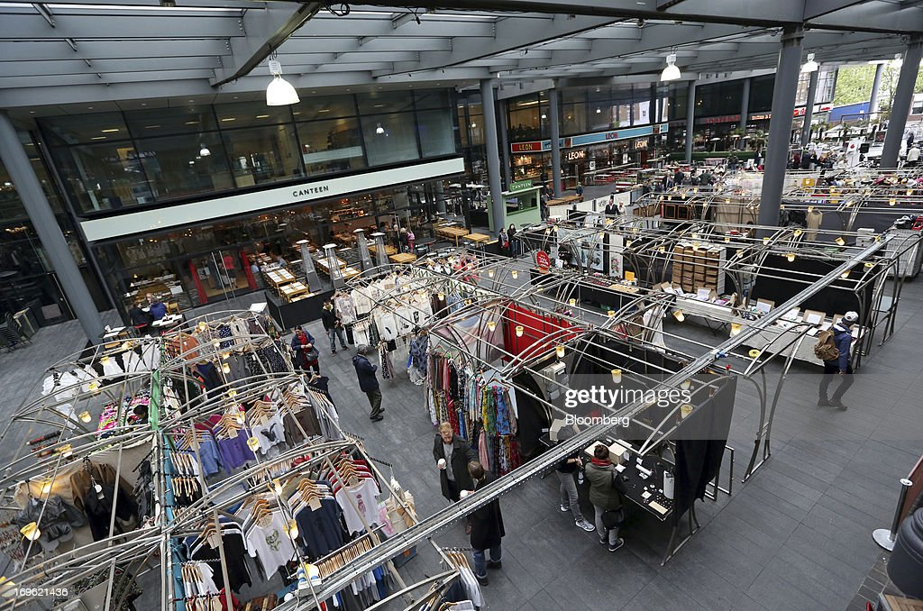 Pedestrians browse items for sale on stalls inside Old Spitalfields Market in London, U.K., on Wednesday, May 29, 2013. Annual U.K. consumer-price inflation slowed to 2.4 percent last month from 2.8 percent in March, the Office for National Statistics said May 21. Photographer: Chris Ratcliffe/Bloomberg via Getty Images