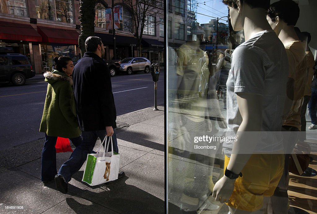 Pedestrians carry a Telus Corp. shopping bag while passing in front of a store on Robson St. in Vancouver, British Columbia, Canada, on Monday, March 25, 2013. Statistics Canada (STCA) is scheduled to release consumer price index data on March 27, 2013. Photographer: Ben Nelms/Bloomberg via Getty Images