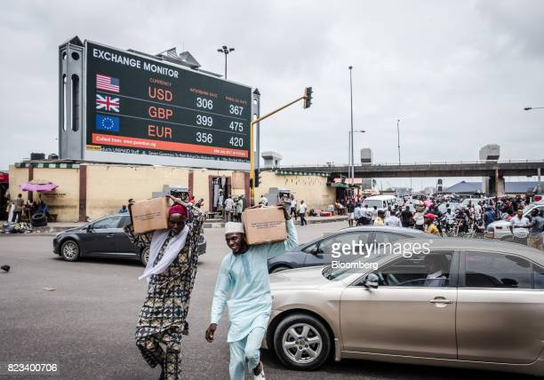 Pedestrians carry boxes of goods across a busy road near a giant advertising screen showing US dollar British pound and euro foreign currency...