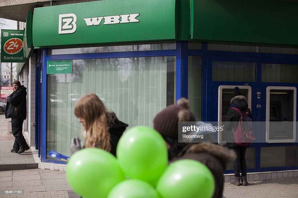 Pedestrians carry green balloons past a Bank Zachodni WBK SA branch in Wroclaw, Poland, on Monday, March 25, 2013. KBC Groep NV of Belgium and Banco Santander SA of Spain raised 4.89 billion zloty ($1.51 billion) from the sale of a stake in Bank Zachodni WBK SA, Poland's third-largest lender. Photographer: Bartek Sadowski/Bloomberg via Getty Images