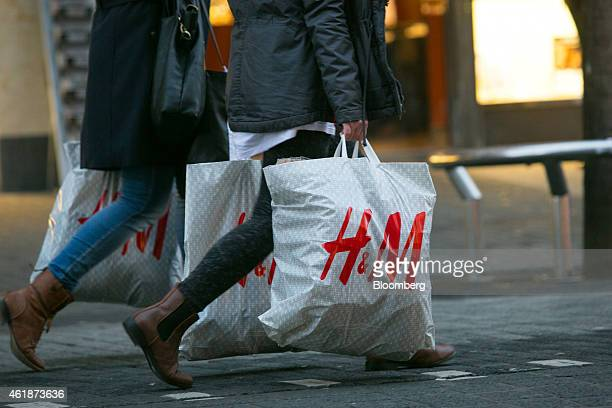 Pedestrians carry Hennes Mauritz AB branded shopping bags in Mannheim Germany on Tuesday Jan 20 2015 German investor confidence jumped to the highest...