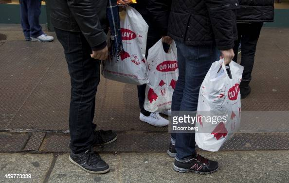 Pedestrians carry Old Navy Inc shopping bags while walking in the Soho neighborhood of New York US on Monday Dec 30 2013 The failure of United Parcel...