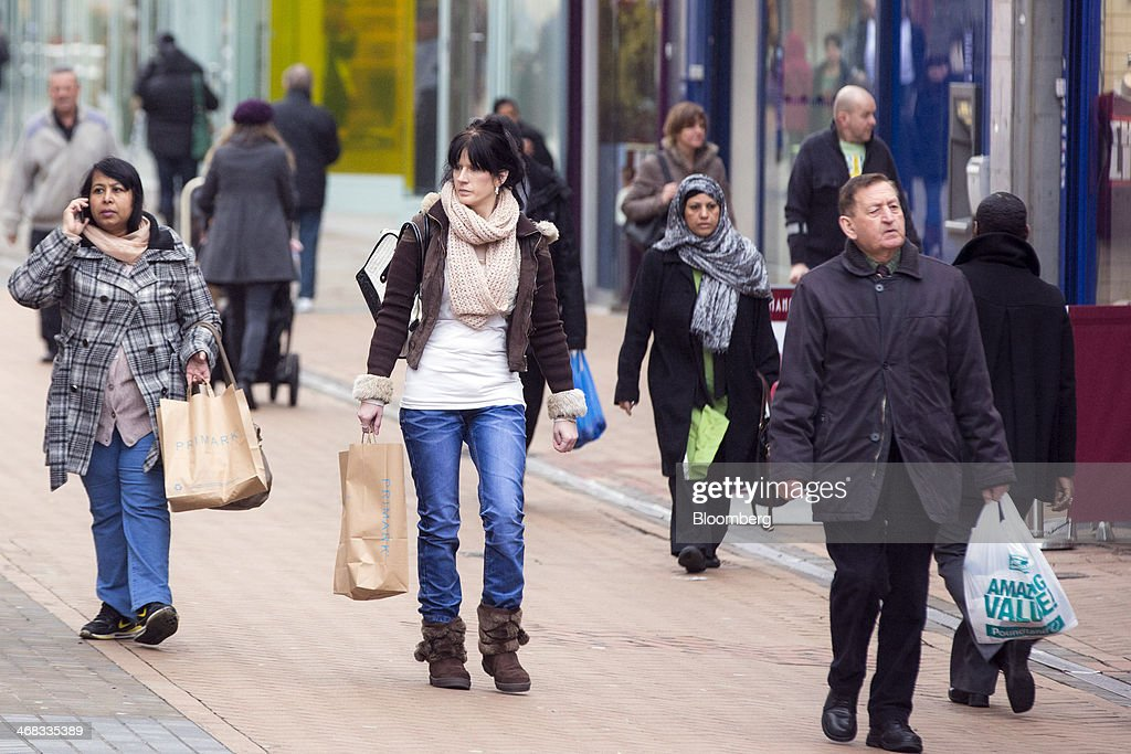Pedestrians carry Primark and Poundland branded shopping bags as they pass stores in Croydon, south London, U.K., on Monday, Feb. 10, 2014. Westfield Group, Australia's biggest mall operator, and Hammerson Plc won preliminary approval to rebuild the Whitgift Centre mall in south London as part of a project valued at about 1 billion pounds ($1.6 billion). Photographer: Jason Alden/Bloomberg via Getty Images