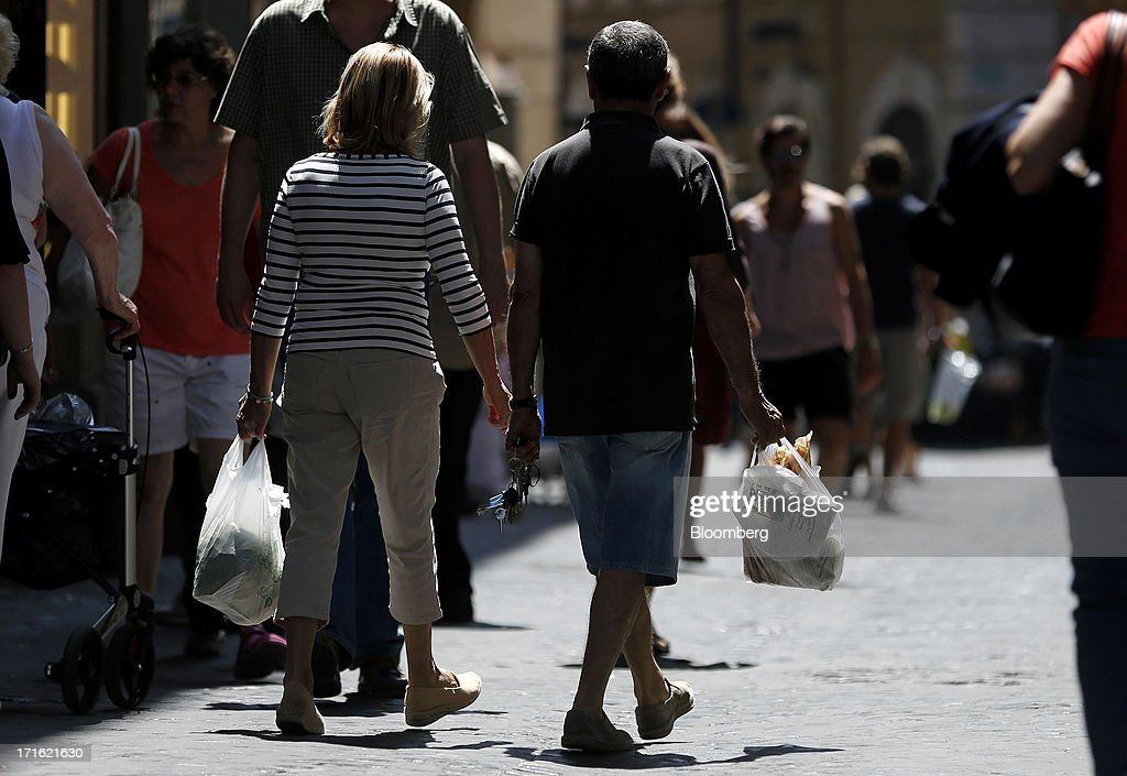 Pedestrians carry produce in shopping bags as they walk past stores in Rome, Italy, on Wednesday, June 26, 2013. Italian household confidence rose this month as consumers grew optimistic about the country's outlook as Prime Minister Enrico Letta's government plans to cut taxes and boost youth employment. Photographer: Alessia Pierdomenico/Bloomberg via Getty Images