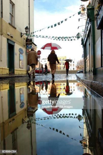 Pedestrians carry raised umbrellas walk past a puddle in Temple Bar Dublin Ireland during periods of heavy showers with intermittent sunny spells