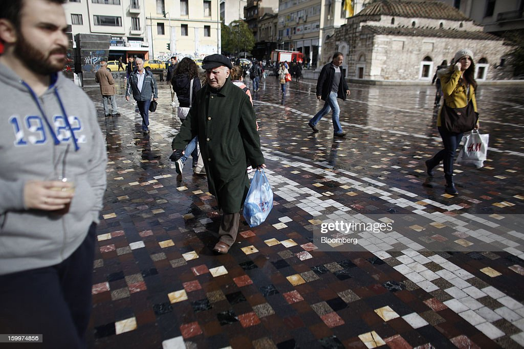 Pedestrians carry shopping bags across a square in central Athens, Greece, on Thursday, Jan. 24, 2013. Greece's government has implemented budget cuts and economic reforms to tame a fiscal deficit that has led to bailouts from the European Union and the International Monetary Fund. Photographer: Kostas Tsironis/Bloomberg via Getty Images