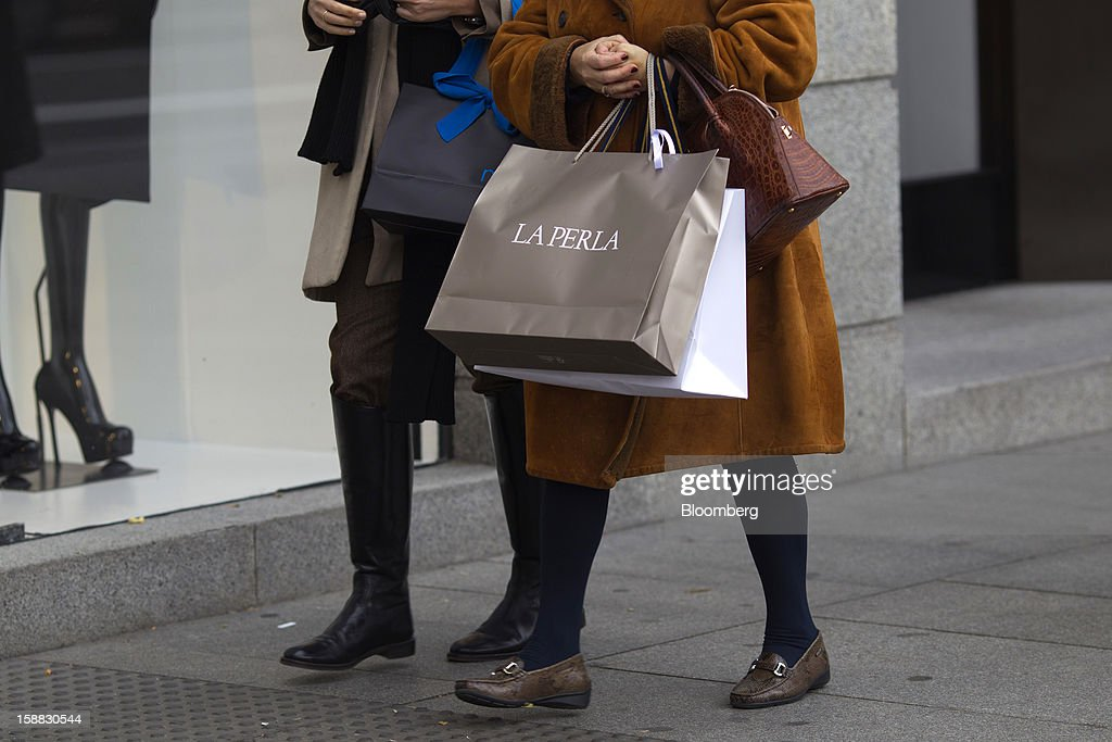 Pedestrians carry shopping bags along a street in central Madrid, Spain, on Saturday, Dec. 29, 2012. Spain's economic activity kept falling in the fourth quarter, Bank of Spain says. Photographer: Angel Navarrete/Bloomberg via Getty Images