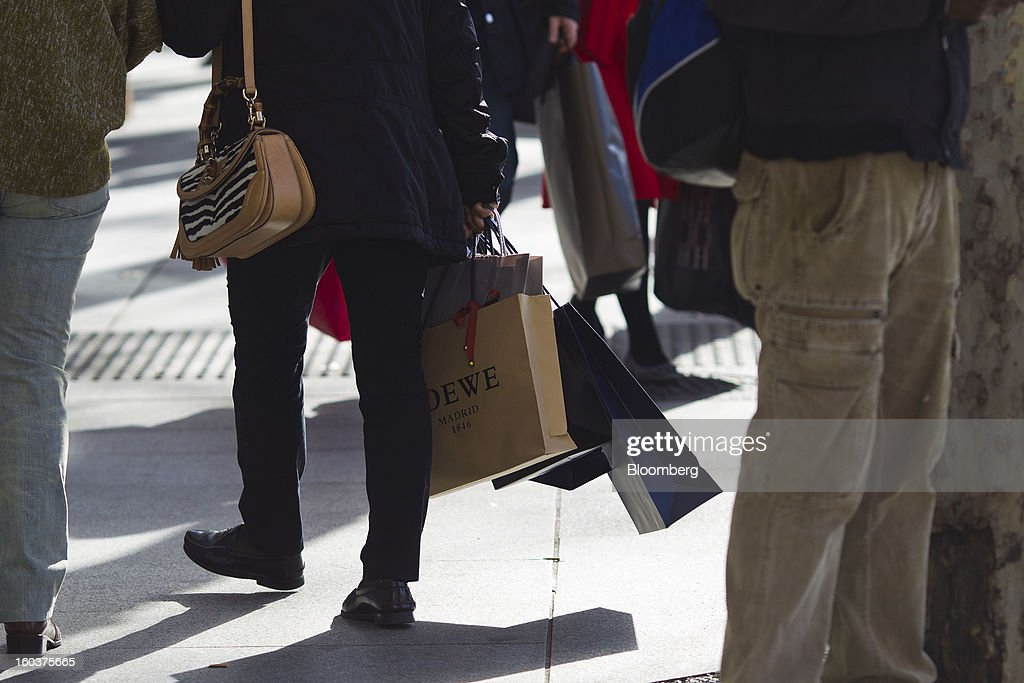 Pedestrians carry shopping bags along a street in central Madrid, Spain, on Wednesday, Jan. 30, 2013. Spain's recession deepened more than economists forecast in the fourth quarter as the government's struggle to rein in the euro region's second-largest budget deficit weighed on domestic demand. Photographer: Angel Navarrete/Bloomberg via Getty Images