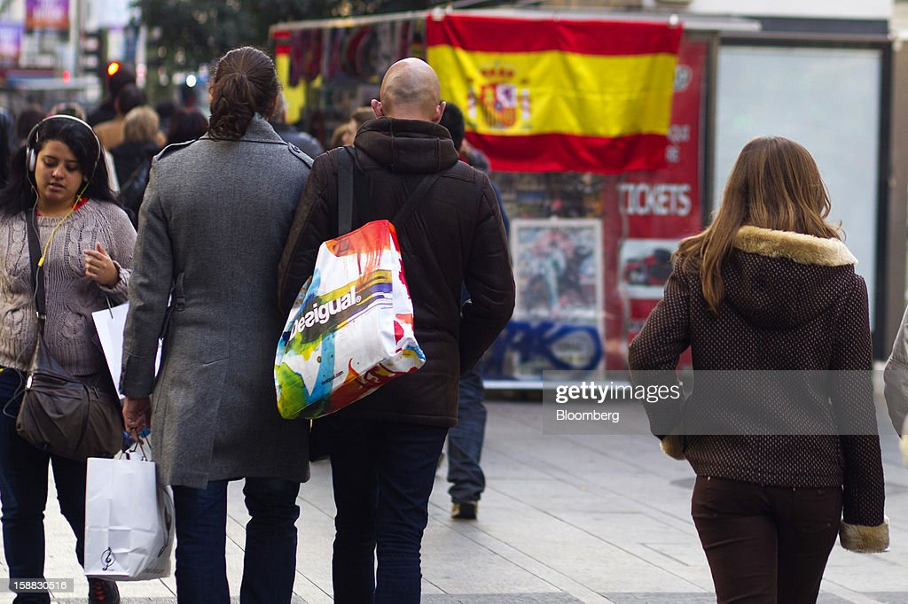 Pedestrians carry shopping bags along a street past a kiosk displaying a Spanish national flag in central Madrid, Spain, on Saturday, Dec. 29, 2012. Spain's economic activity kept falling in the fourth quarter, Bank of Spain says. Photographer: Angel Navarrete/Bloomberg via Getty Images