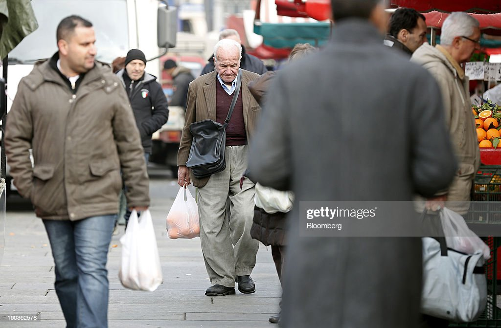 Pedestrians carry shopping bags as they pass an outdoor market in Turin, Italy, on Tuesday, Jan. 29, 2013. Italy sold 8.5 billion euros ($11.4 billion) of six-month Treasury bills as rates dropped to the lowest in almost three years as the European Central Bank's pledge to buy bonds continues to provide an effective backstop even amid rising political concerns. Photographer: Alessia Pierdomenico/Bloomberg via Getty Images