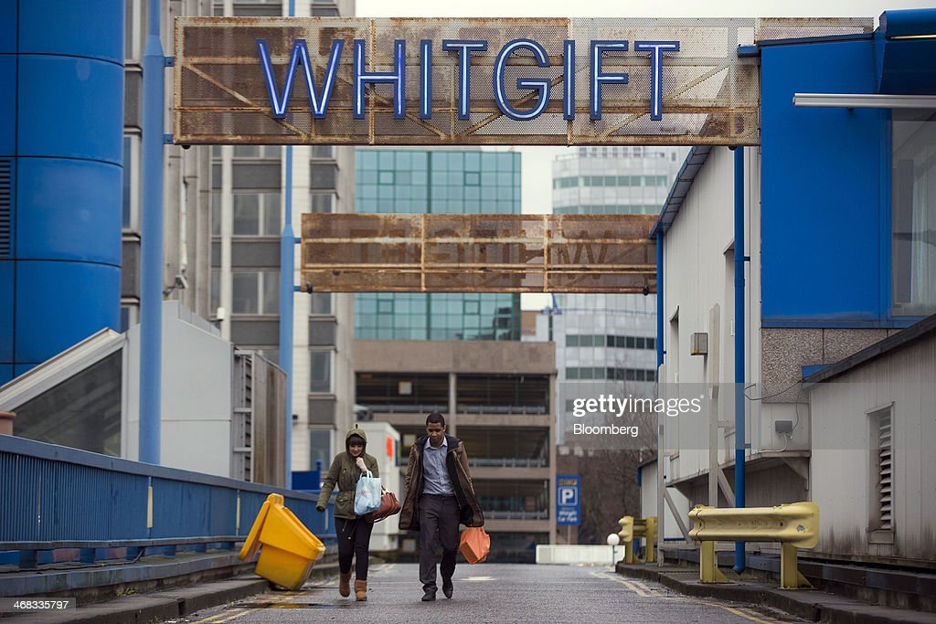 Pedestrians carry shopping bags as they walk beneath a sign for the Whitgift Centre shopping mall in Croydon, south London, U.K., on Monday, Feb. 10, 2014. Westfield Group, Australia's biggest mall operator, and Hammerson Plc won preliminary approval to rebuild the Whitgift Centre mall in south London as part of a project valued at about 1 billion pounds ($1.6 billion). Photographer: Jason Alden/Bloomberg via Getty Images