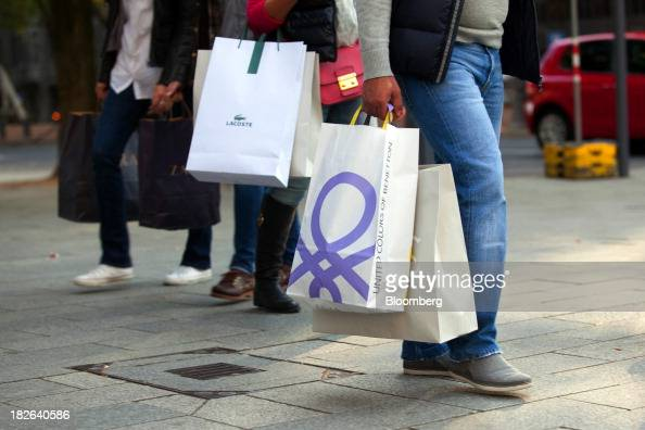 Pedestrians carry shopping bags for Lacoste SA center and United Colors of Benetton operated by Benetton Group SpA right in Dusseldorf Germany on...