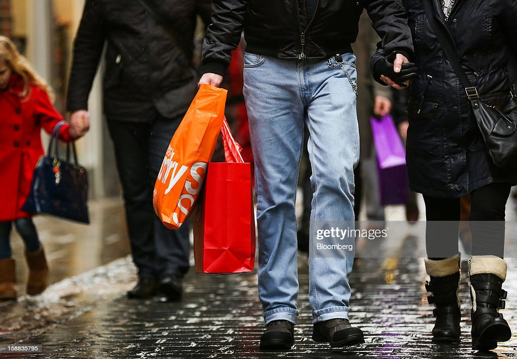Pedestrians carry shopping bags in the Covent Garden district of London, U.K., on Monday, Dec. 31, 2012. The number of Britons making shopping trips for post-holiday bargains barely increased on the day after Christmas as more people sought discounts online. Photographer: Jason Alden/Bloomberg via Getty Images