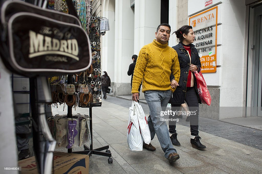 Pedestrians carry shopping bags past a street vendor's display of souvenir items for sale in Madrid, Spain, on Wednesday, April 3, 2013. Prime Minister Mariano Rajoy told Spaniards they'll start to see the benefits of his reform program next year after he avoided becoming the fifth European leader to request a full sovereign rescue. Photographer: Angel Navarrete/Bloomberg via Getty Images
