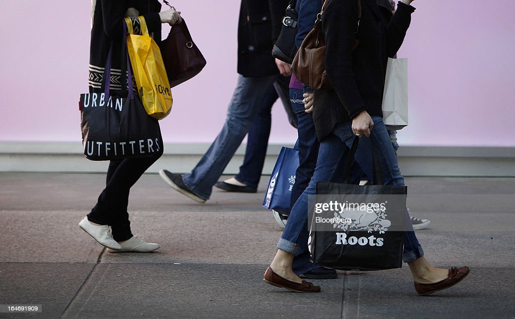 Pedestrians carry shopping bags while walking on Robson St. in Vancouver, British Columbia, Canada, on Monday, March 25, 2013. Statistics Canada (STCA) is scheduled to release consumer price index data on March 27, 2013. Photographer: Ben Nelms/Bloomberg via Getty Images