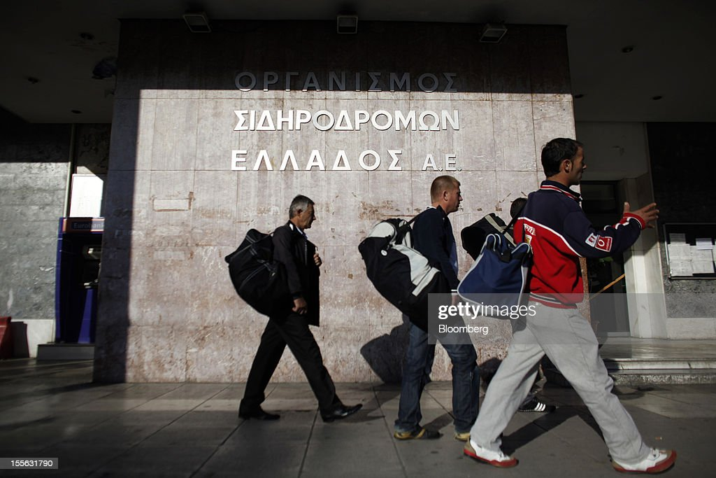 Pedestrians carry their luggage bags past the central train station at the start of a general strike in Athens, Greece, on Tuesday, Nov. 6, 2012. Greece headed for a cliffhanger vote on austerity measures needed to keep the bailout on track as a 48-hour general strike began and European officials squabbled over the timing of a deal to unlock rescue funds. Photographer: Kostas Tsironis/Bloomberg via Getty Images