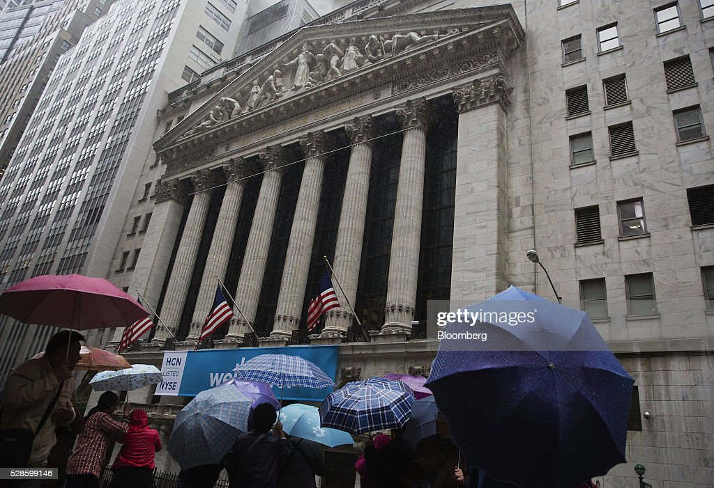 Pedestrians carry umbrellas while walking in front of the New York Stock Exchange (NYSE) in New York, U.S., on Friday, May 6, 2016. U.S. stocks retreated a fourth day, with the S&P 500 poised for its first back-to-back weekly drop since February, after the smallest jobs gain in seven months raised doubts about the strength of the worlds largest economy. Photographer: Victor J. Blue/Bloomberg via Getty Images