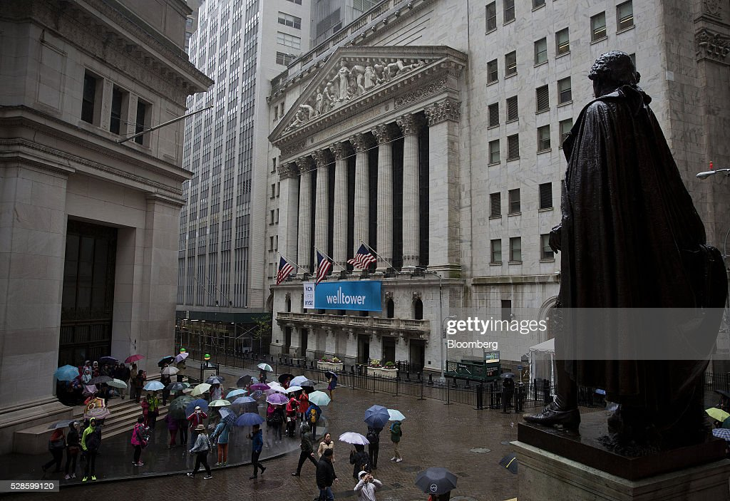 Pedestrians carry umbrellas while walking past the New York Stock Exchange (NYSE) in New York, U.S., on Friday, May 6, 2016. U.S. stocks retreated a fourth day, with the S&P 500 poised for its first back-to-back weekly drop since February, after the smallest jobs gain in seven months raised doubts about the strength of the worlds largest economy. Photographer: Victor J. Blue/Bloomberg via Getty Images