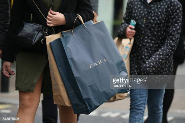 Pedestrians carrying shopping bags in Oxford Street in London on October 27 2016 Britain's economy won a double boost on October 27 on news of...