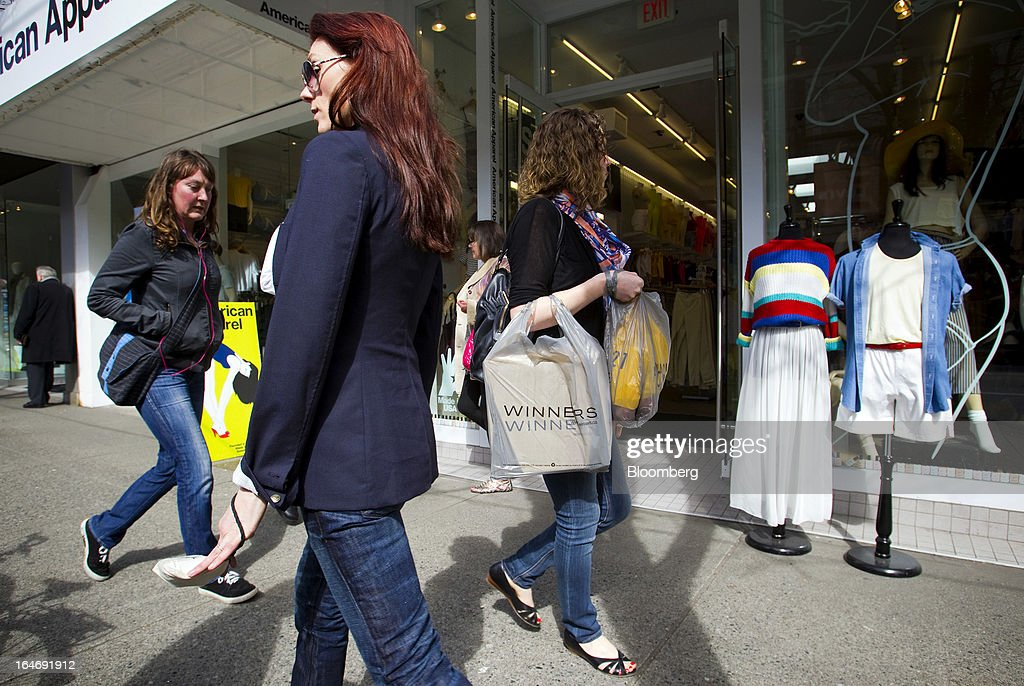 Pedestrians carrying shopping bags pass in front of an American Apparel Inc. store on Robson St. in Vancouver, British Columbia, Canada, on Monday, March 25, 2013. Statistics Canada (STCA) is scheduled to release consumer price index data on March 27, 2013. Photographer: Ben Nelms/Bloomberg via Getty Images