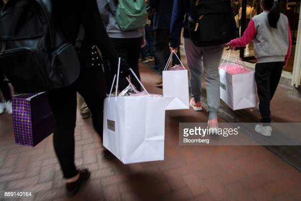 Pedestrians carrying shopping bags walk along a road in Hong Kong China on Saturday Dec 9 2017 With more Chinese tourists likely to travel to Hong...
