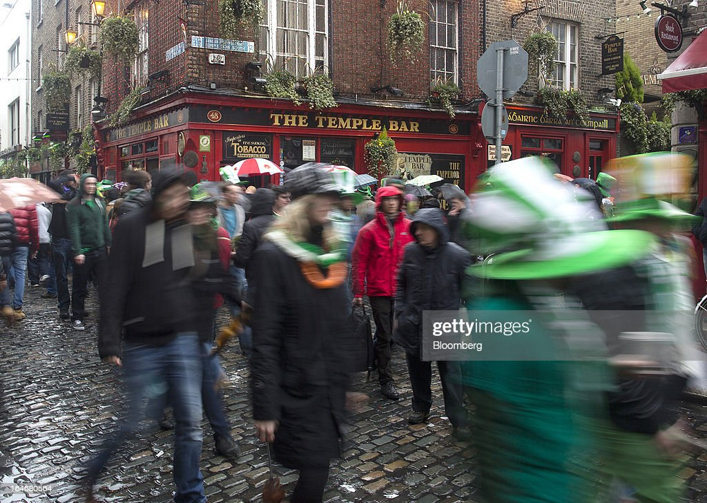 Pedestrians carrying umbrellas and wearing St. Patrick's day hats and scarves move past the Temple Bar public house in Dublin, Ireland, on Sunday, March 17, 2013. Ireland's renewed competiveness makes it a beacon for the U.S. companies such as EBay, Google Inc. and Facebook Inc., which have expanded their operations in the country over the past two years. Photographer: Simon Dawson/Bloomberg via Getty Images