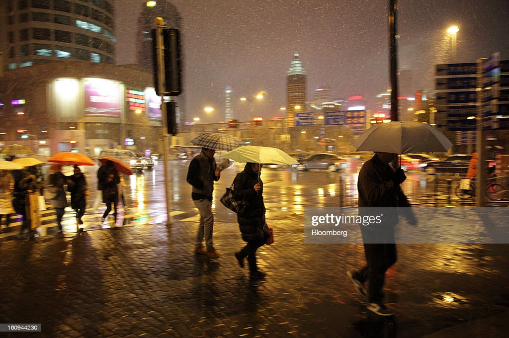 Pedestrians carrying umbrellas cross a road as snow falls in Shanghai, China, on Thursday, Feb. 7, 2013. China's economic growth accelerated for the first time in two years as government efforts to revive demand drove a rebound in industrial output, retail sales and the housing market. Photographer: Tomohiro Ohsumi/Bloomberg via Getty Images