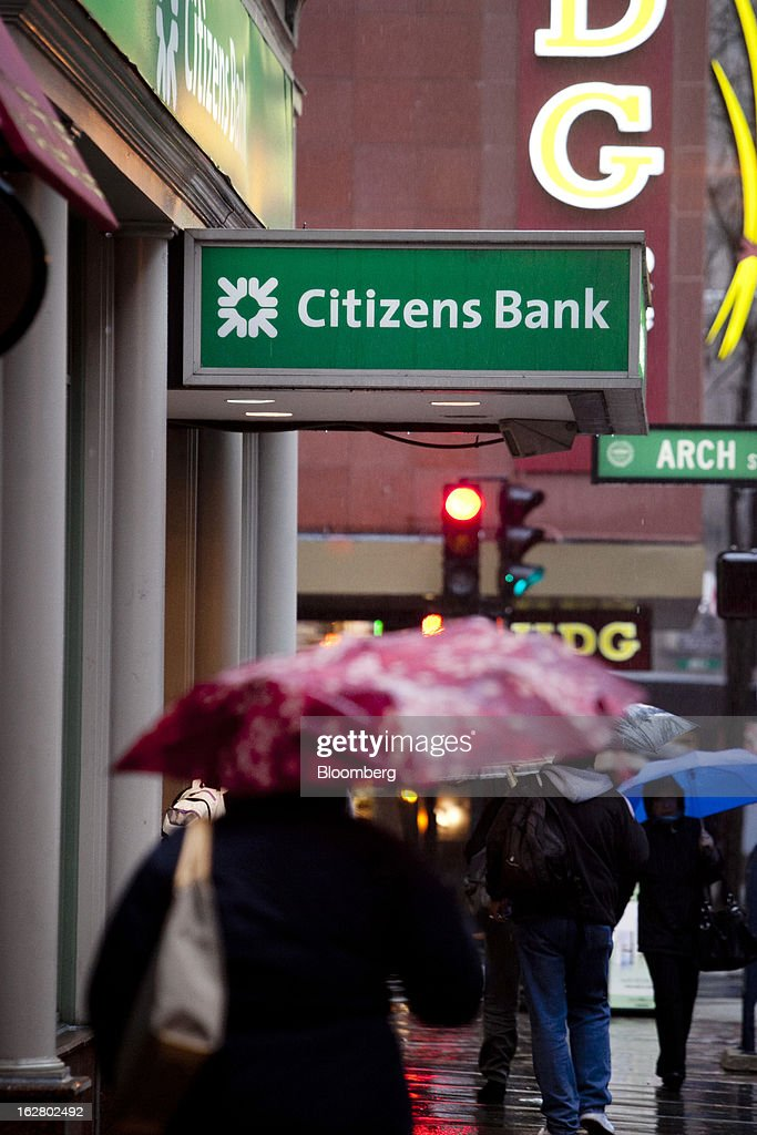 Pedestrians carrying umbrellas pass in front of a Citizens Financial Group Inc. bank branch in Boston, Massachusetts, U.S., on Wednesday, Feb. 27, 2013. Royal Bank of Scotland Group Plc will this week announce plans to sell a stake in Citizens Financial Group Inc. and shrink assets at its investment-bank by as much as 30 billion pounds, said a person with knowledge of the plans, who asked not to be identified because the matter is private. Photographer: Kelvin Ma/Bloomberg via Getty Images