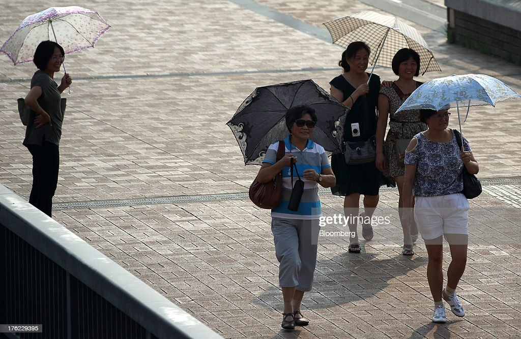 Pedestrians carrying umbrellas stroll along a street in Tokyo, Japan, on Monday, Aug. 12, 2013. Japan's economy slowed more than forecast in the second quarter as businesses cut investment, undermining gains in consumer and government spending that helped reduce deflationary pressures. Photographer: Tomohiro Ohsumi/Bloomberg via Getty Images