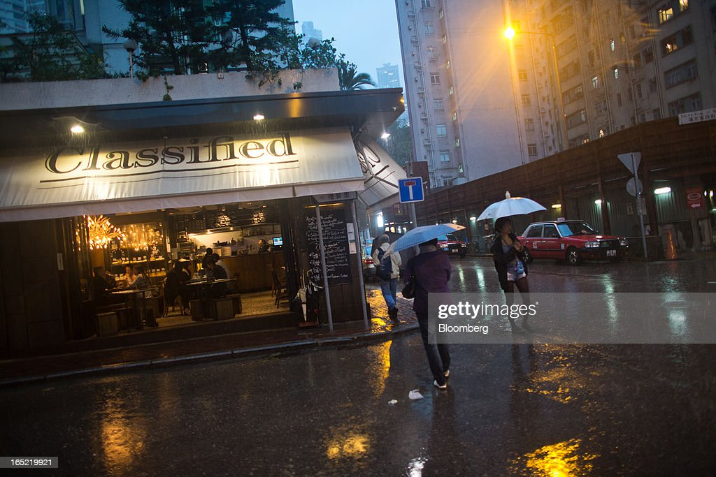 Pedestrians carrying umbrellas walk past a Classified cafe, operated by Press Room Group, as rain falls in the Tai Hang area of Hong Kong, China, on Saturday, March 30, 2013. Rents are climbing in neighborhoods near Causeway Bay and Hong Kong's other prime shopping districts, known for luxury stores that attract free-spending tourists from mainland China. That's squeezing out mom-and-pop shops, congee and noodle vendors as developers and landlords seek to profit from the trend. Photographer: Lam Yik Fei/Bloomberg via Getty Images