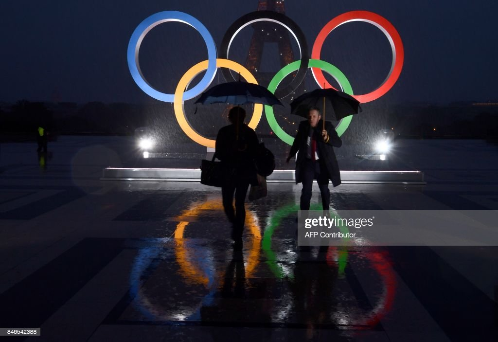 Pedestrians carrying umbrellas walk past the Olympics Rings on the Trocadero Esplanade near the Eiffel Tower in Paris, on September 13, 2017, after the International Olympic Committee named Paris host city of the 2024 Summer Olympic Games. The International Olympic Committee named Paris and Los Angeles as hosts for the 2024 and 2028 Olympics on September 13, 2017, crowning two cities at the same time in a historic first for the embattled sports body. /