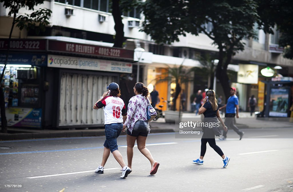 Pedestrians chat on mobile phones while crossing the street in the Ipanema neighborhood of Rio de Janeiro, Brazil, on Tuesday, Aug. 6, 2013. Telefonica Brasil SAs Vivo, now controlling 28.7 percent of Brazil's mmobile phone market is locked in a battle with Tim Participacoes SA, whose share of the market has risen to 27.2 percent by undercutting rivals on voice and data plans. Photographer: Lianne Milton/Bloomberg via Getty Images