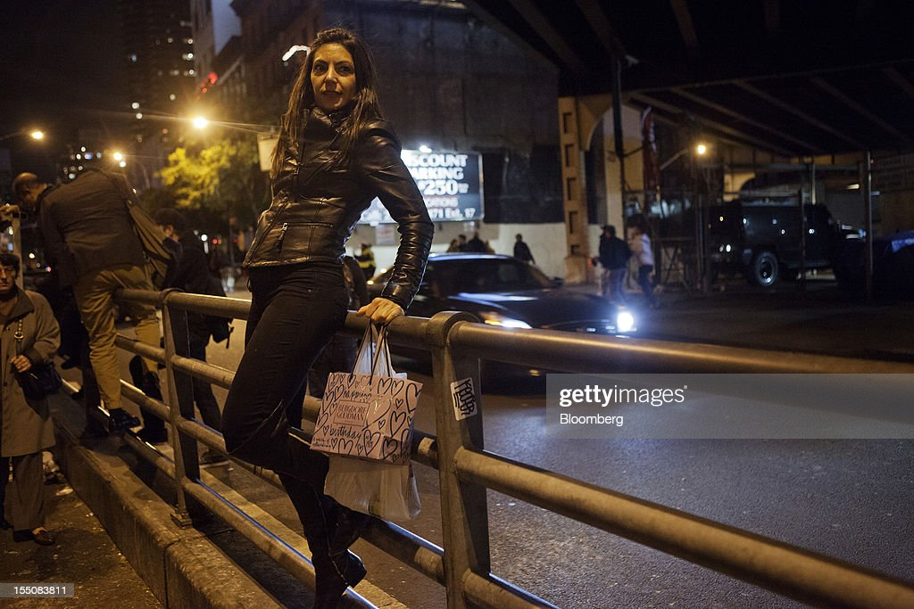 Pedestrians climb over railings as they make their way over the Ed Koch Queensboro Bridge in New York, U.S., on Wednesday, Oct. 31, 2012. Atlantic superstorm Sandy may cut U.S. economic growth as it keeps millions of employees away from work and shuts businesses from restaurants to refineries in one of the nation's most populated and productive regions. Photographer: Victor J. Blue/Bloomberg via Getty Images