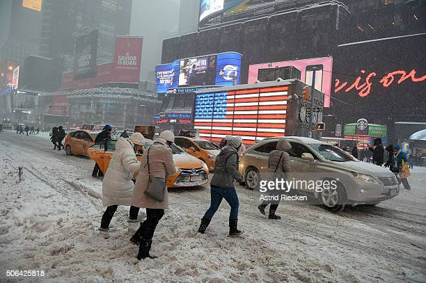 Pedestrians cope with snow covering sidewalks and streets in Time Square on January 23 2016 in New York City A major Nor'easter is hitting much of...