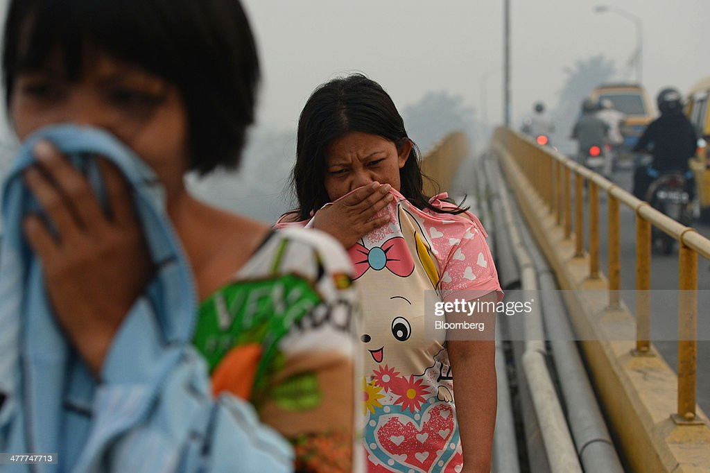 Pedestrians cover their faces as they cross a bridge over the Siak river shrouded in haze in Pekanbaru, Riau Province, Indonesia on Friday, March 7, 2014. Indonesian central bank Governor Agus Martowardojo embarked on the country's most aggressive rate-increase cycle in eight years within a month of taking the helm in May to shore up the rupiah and damp price pressures. Photographer: Dimas Ardian/Bloomberg via Getty Images