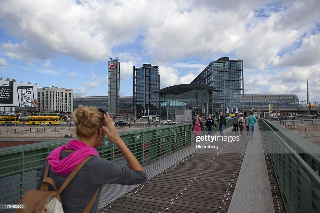 Pedestrians cross a bridge as Berlin Central Station, also known as Hauptbahnhof, stands beyond in Berlin, Germany, on Tuesday, Aug. 13, 2013. German gross domestic product rose 0.7 percent from the first quarter and the French economy expanded 0.5 percent, the countries' national statistics offices said today. Photographer: Krisztian Bocsi/Bloomberg via Getty Images