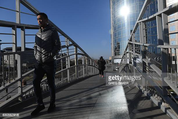 Pedestrians cross a bridge on a sunny day in Beijing on December 27 2016 China has passed a law that levies taxes on pollution but ignores carbon...